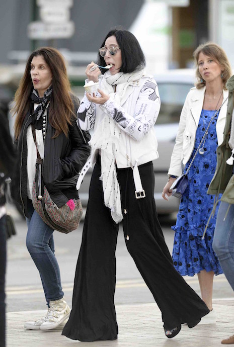 Cher enjoys ice cream as she walks through the coastal town